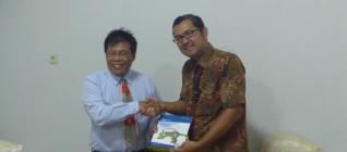 Ketua Tim Peneliti Hikom HI BINUS menyerahkan pamflet BINUS kepada Ketua Jurusan HI UNS Prof Andrik Purwasito DEA 23 April 2013