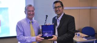 pemberian token of appreciation oleh Dr. Tirta Mursitama kepada Prof. Ron Matthews