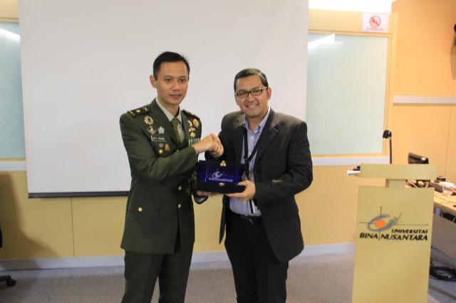 Pemberika token of appreciation oleh Kepala Departmen Hubungan Internasional BINUS, Tirta Nugraha Mursitama, PhD kepada Mayor Agus Yudhoyono