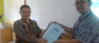 Dr. Guido Benny gives a token of appreciation to Tirta Mursitama, Phd