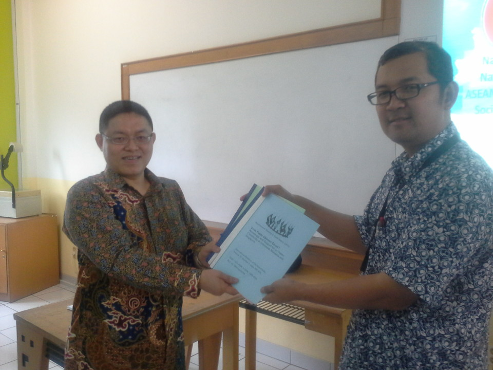 Dr. Guido Benny gives a token of appreciation to Tirta Mursitama, Phd